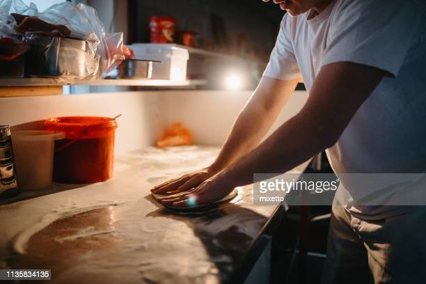 chef makes a dough for pizza - pizzeria stock pictures, royalty-free photos & images