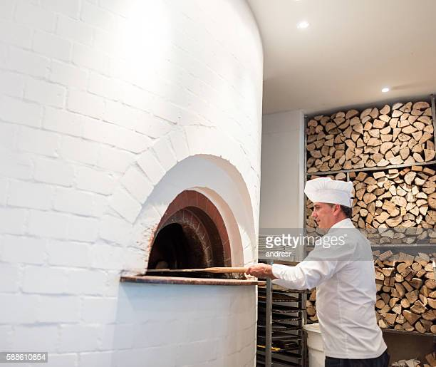 Chef making pizza in a wooden oven