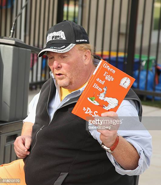 Chef Mario Batali holds up the book Green Eggs and Ham by Dr Seuss during the opening of the Books for Kids/Mario Batali Foundation Library at the...
