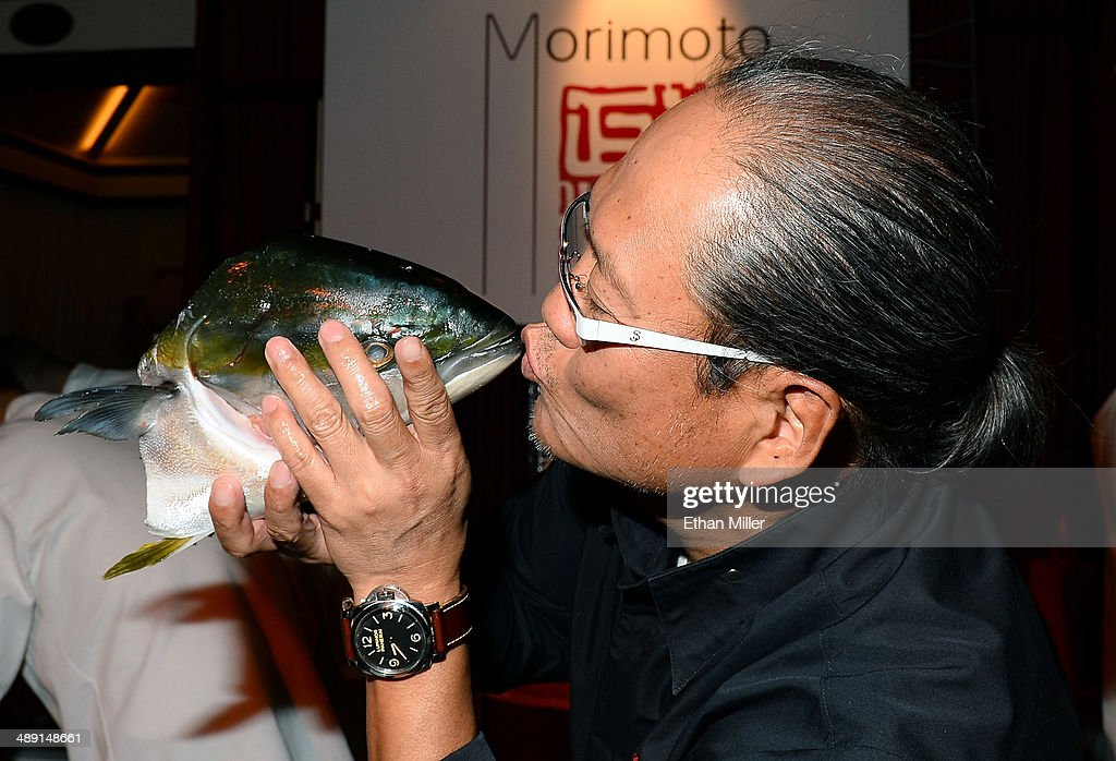 Chef Masaharu Morimoto kisses a fish head at his booth at Vegas Uncork'd by Bon Appetit's Grand Tasting event at Caesars Palace on May 9, 2014 in Las Vegas, Nevada.