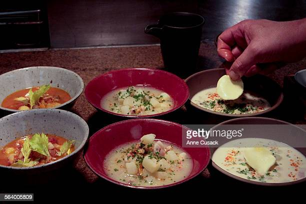 Chef Michael Cimarusti places a pad of butter on the New England creamy Clam Chowder right New England Calm Chowder clear center and Manhattan Clam...