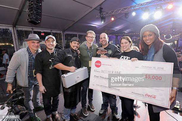 Chef Michael Symon and Chef Bobby Flay pose onstage with Winners of both the Coke and Smoke BBQ Challenge and Thrillist's People's Choice Award Chef...