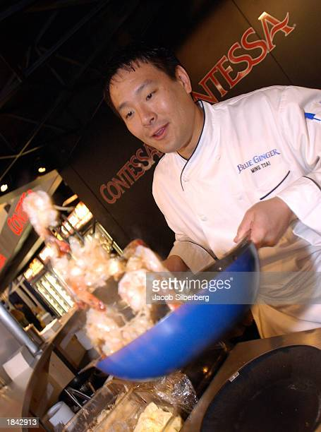 Chef Ming Tsai who hosts the show East Meets West on the Food Network cooks shrimp at the Boston International Seafood Show in Boston Massachusetts...