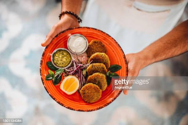 chef erbjuder sin förberedda falafel plate - bulgur bildbanksfoton och bilder
