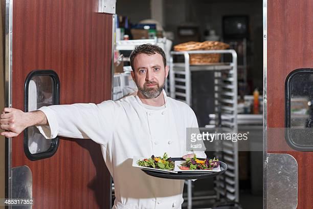 Chef oder Kellner im restaurant tragen Teller mit Essen