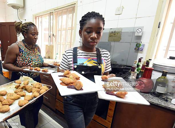 Chef Ozoz Sokoh's daughter Jedidiah carries food to serve clients at Strangers restaurant in Lagos on January 30 2016 During the week Ozoz Sokoh...