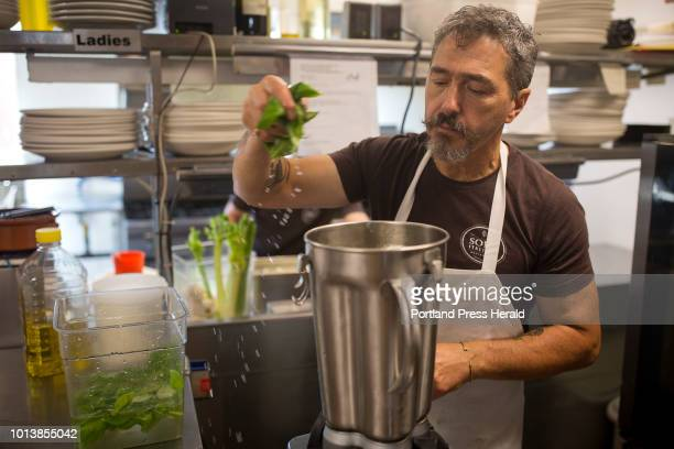 Chef Paolo adds Genovese basil leaves that have been soaking in water to the mixture of pine nuts and olive oil at Solo Italiano on Tuesday August...