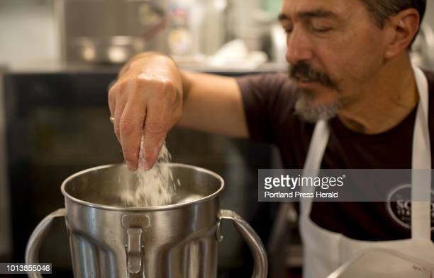 Chef Paolo Laboa folds in two kinds of freshly grated cheese parmigiano reggiano and pecorino sardo to the olive oil pine nut and basil mixture at...