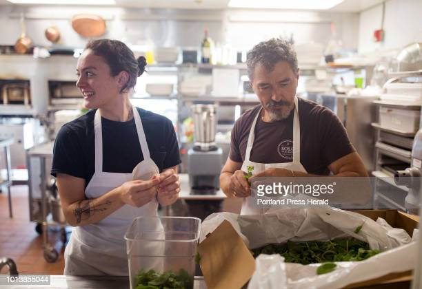 Chef Paolo Laboa right and line cook Ruth Connelly remove the Genovese basil leave from the stems before making his family Genovese pesto recipe at...
