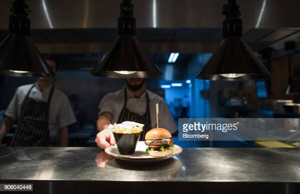 A chef places a burger and fries on to the pass at a Bar and Block restaurant operated by Whitbread Plc in London UK on Wednesday Jan 17 2018 The...