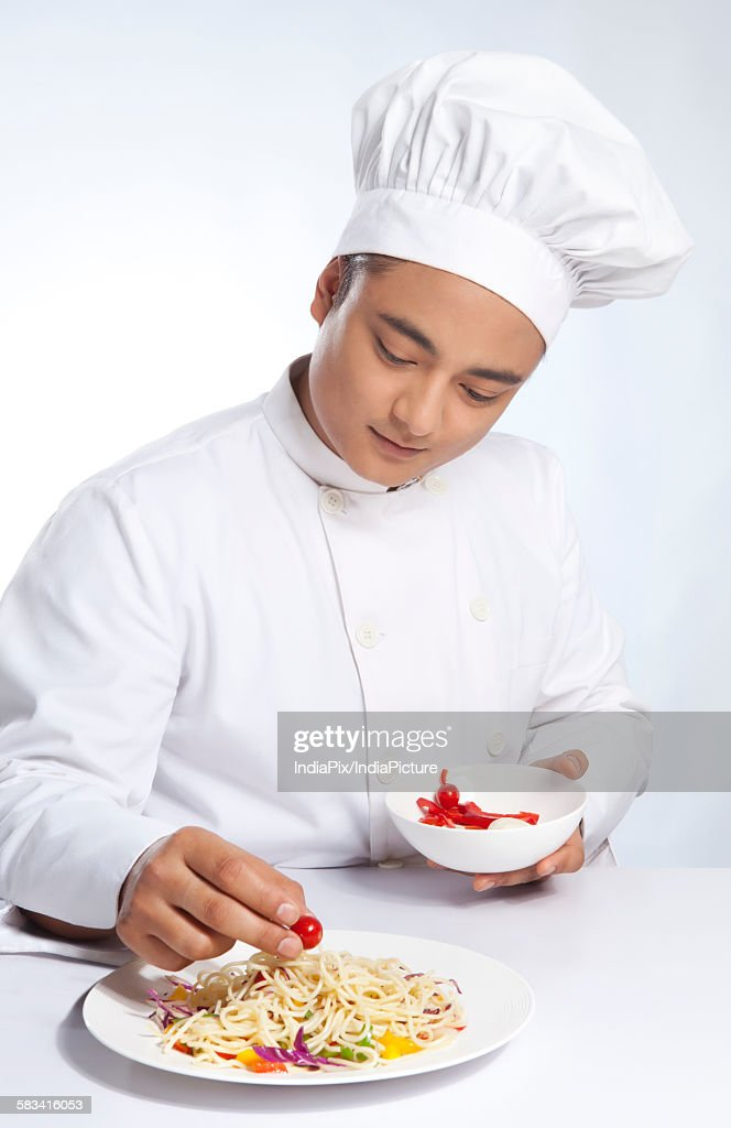 Chef placing cherry tomato on plate of noodles : Stock Photo