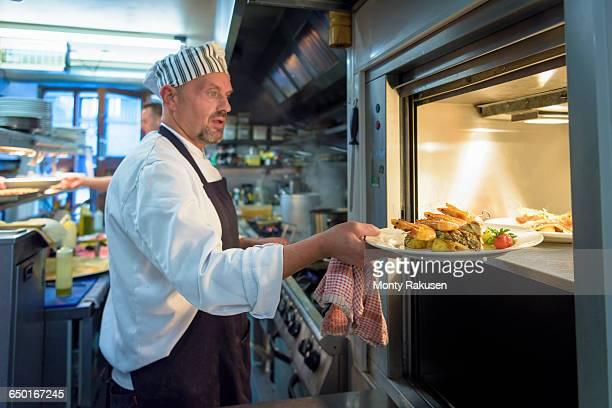 chef placing dish in lift in traditional italian restaurant kitchen - オトレイ ストックフォトと画像