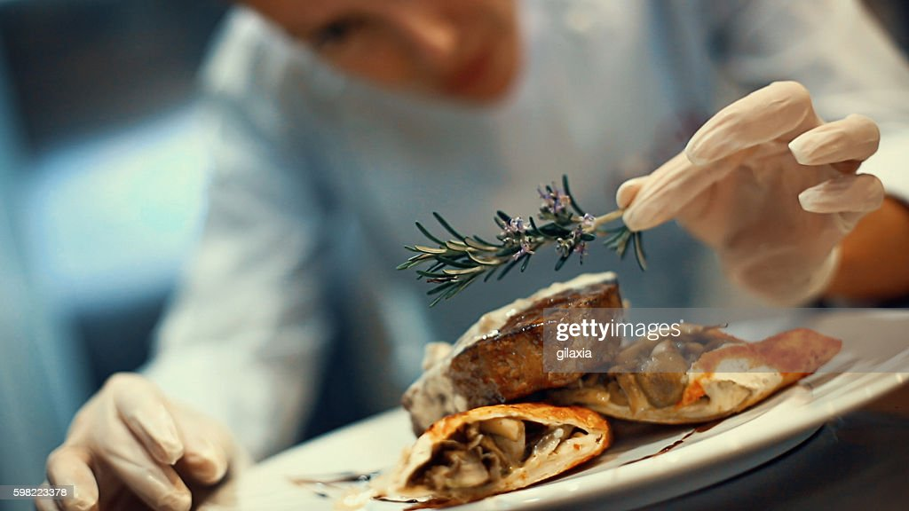 Chef placing finishing touches on a meal. : Stockfoto