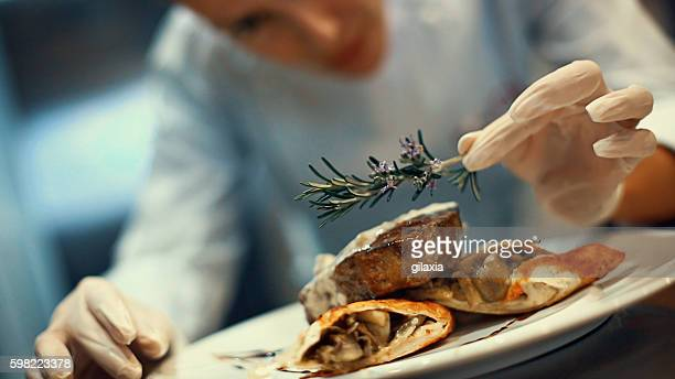 chef placing finishing touches on a meal. - dranken en maaltijden stockfoto's en -beelden