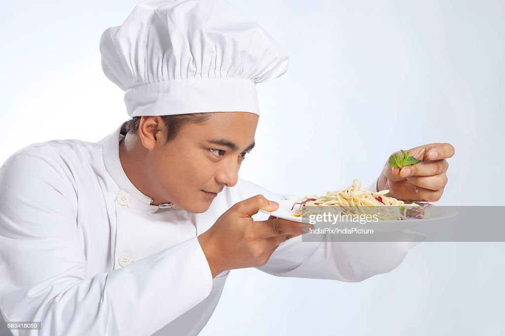 Chef placing leaf on plate of noodles : Stock Photo
