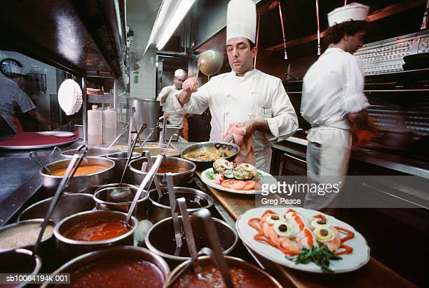 Chef plating dinners with staff in commercial kitchen