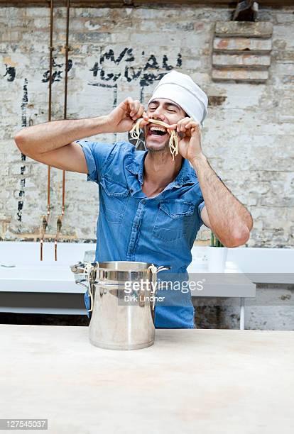 le chef jouant avec des spaghettis en cuisine - cuisine humour photos et images de collection
