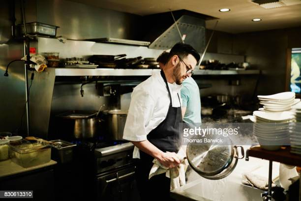 Chef pouring boiling water in sink while preparing for dinner service in restaurant kitchen