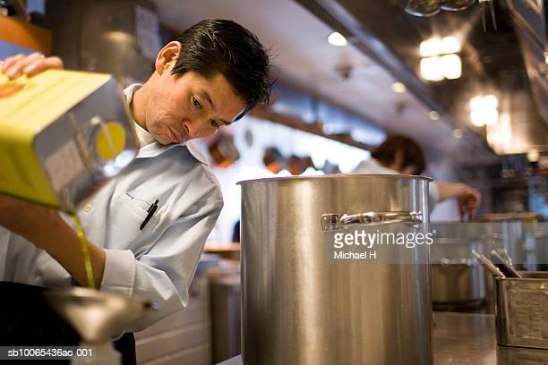chef pouring olive oil into bottle in kitchen - stew pot stock pictures, royalty-free photos & images