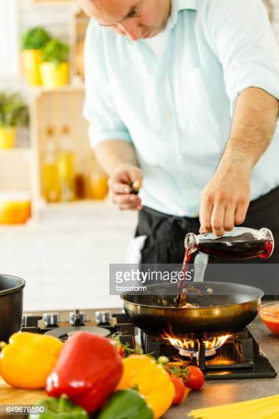 Chef à verser le vin rouge en direction de poêle à frire