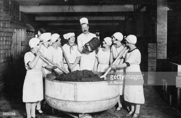 A chef pouring rum into 600 pounds of fruit being mixed for Christmas puddings for a feast at Cadby Hall