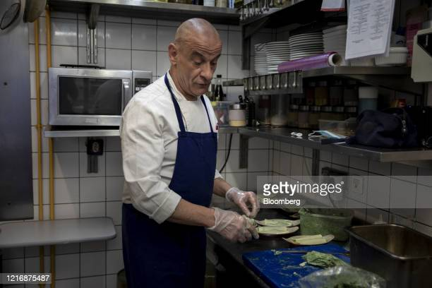 Chef prepares a dish of pasta with spinach in a restaurant kitchen as France reopens cafes and restaurants for business in Paris, France, on Tuesday,...