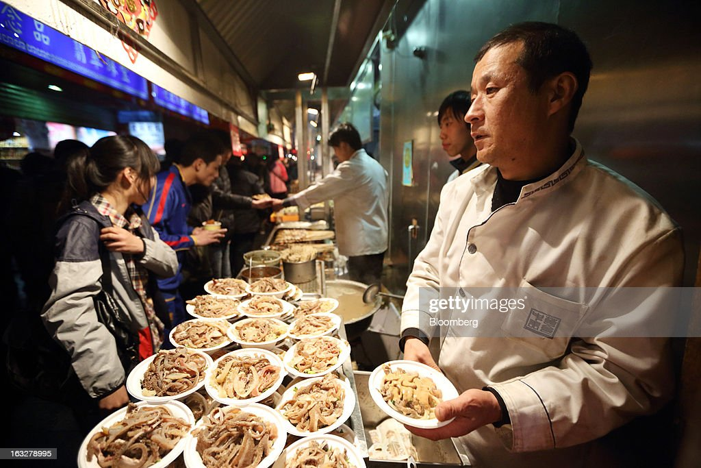A chef prepares dishes at a restaurant at night in Beijing, China, on Wednesday, March 6, 2013. China maintained its economic-growth target at 7.5 percent for 2013 while setting a lower inflation goal of 3.5 percent, setting up a challenge for new leaders to keep prices in check without harming expansion. Photographer: Tomohiro Ohsumi/Bloomberg via Getty Images