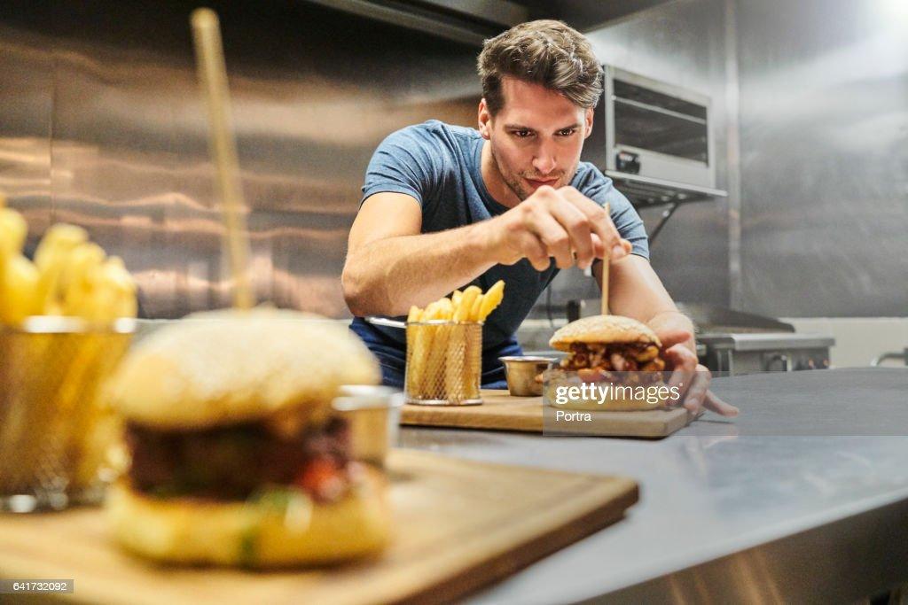 Chef preparing burger on plate at restaurant : Stock Photo