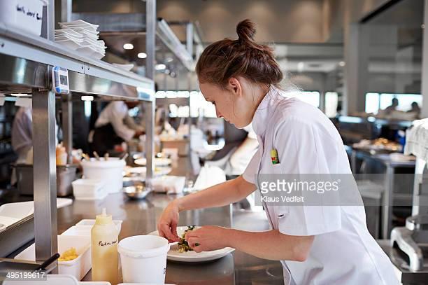 Chef preparing dish in kitchen at restaurant