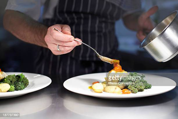 chef preparing dish in kitchen - seafood stock pictures, royalty-free photos & images