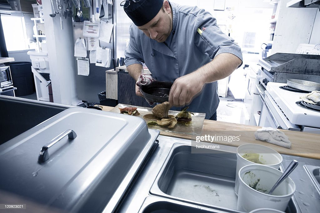 Chef preparing food in a restaurant : Stock Photo
