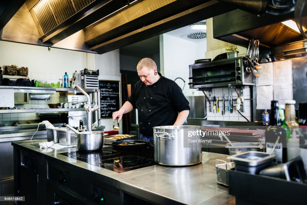 Chef Preparing Food In Modern Restaurant Kitchen High Res Stock Photo Getty Images