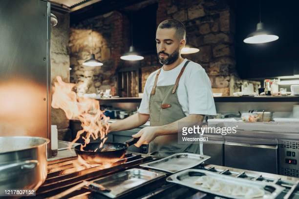 chef preparing food in restaurant kitchen - chef foto e immagini stock