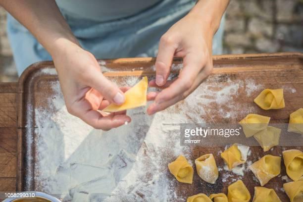 chef preparing handmade stuffed pasta tortellini - tradizione foto e immagini stock
