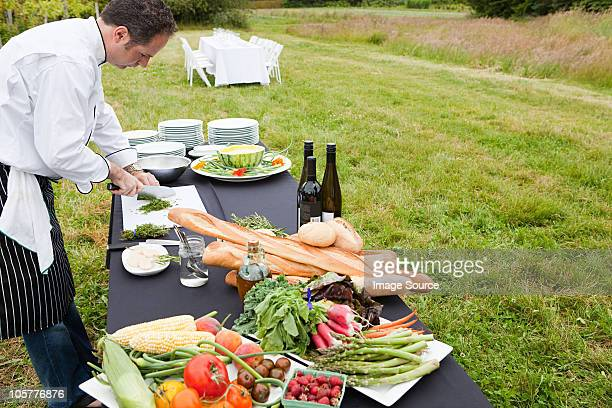 chef preparing meal in a field - farm to table stock photos and pictures