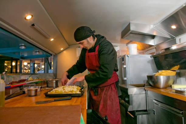 Chef preparing pizza in food stall van at night