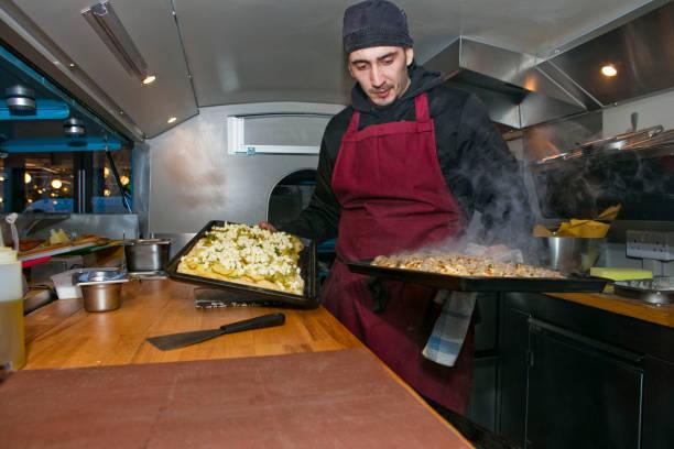 Chef preparing pizzas in food stall van at night