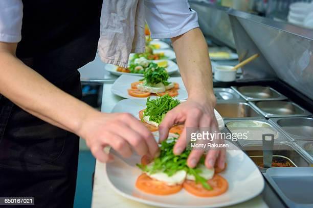 chef preparing salad dish in traditional italian restaurant kitchen, close up - monty rakusen stock-fotos und bilder
