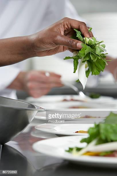 Chef preparing salad in kitchen close-up