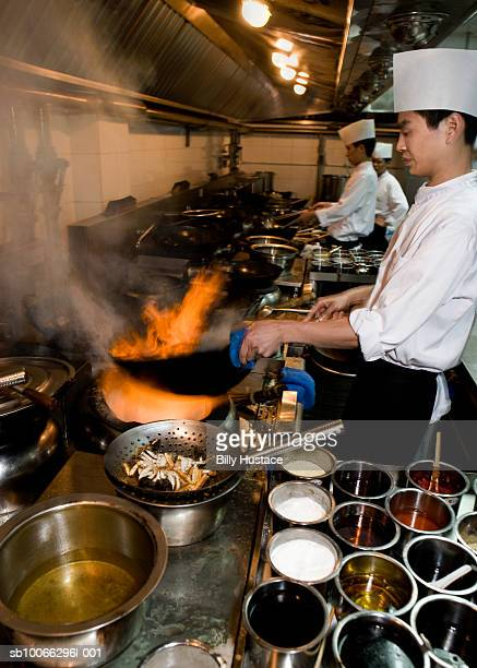 Chef preparing stir-fried food in kitchen