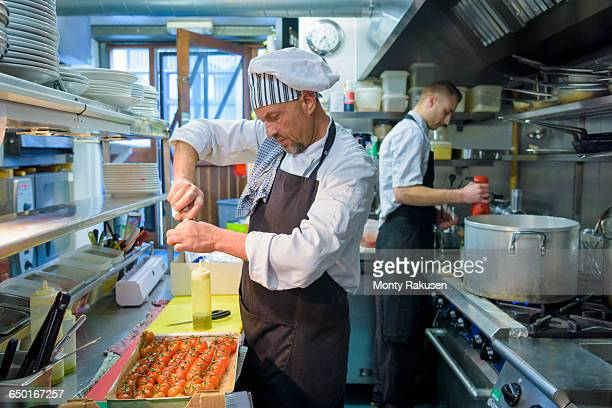 chef preparing tomatoes in traditional italian restaurant kitchen - オトレイ ストックフォトと画像