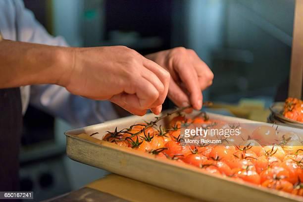 chef preparing tomatoes in traditional italian restaurant kitchen, close up - monty rakusen stock-fotos und bilder