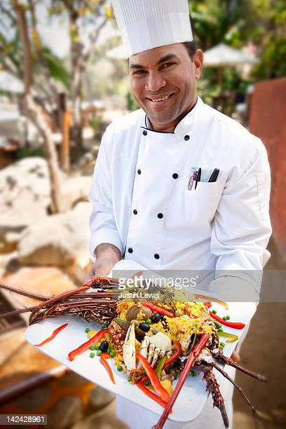 Chef presenting a plate of sea food paiya