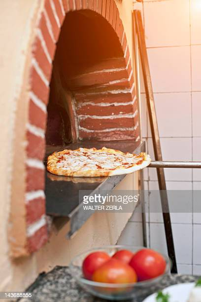Chef pulling pizza from oven