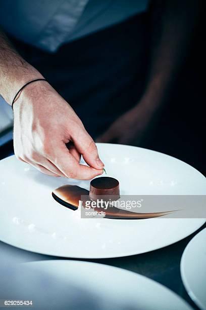 chef putting a green leaf on chocolate dessert - nagerecht stockfoto's en -beelden