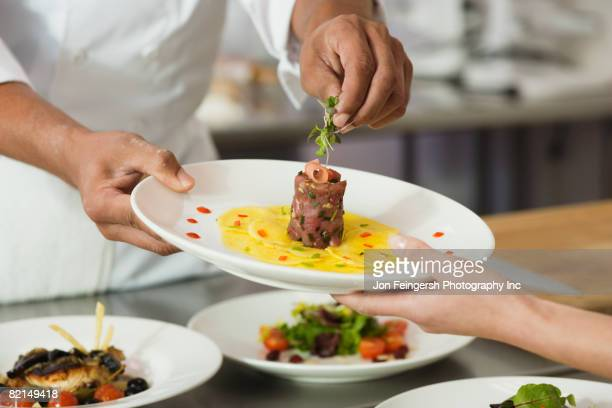 chef putting garnish on plate of food - fine dining stock pictures, royalty-free photos & images