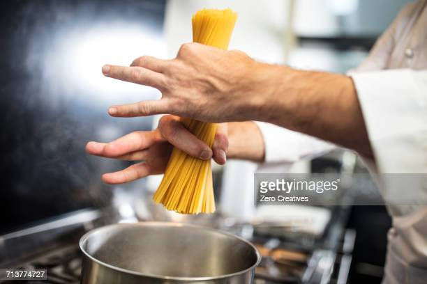 chef putting spaghetti in saucepan on stove, close-up, overhead view - saucepan stock pictures, royalty-free photos & images