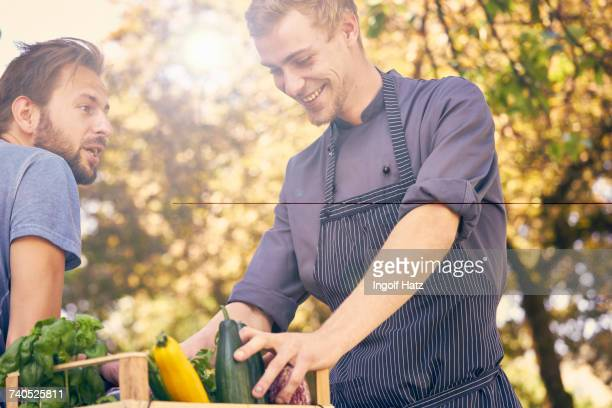 Chef receiving delivery of crate of vegetables