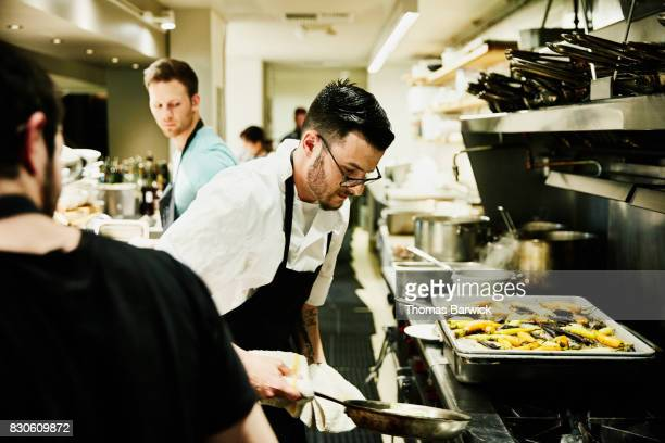 Chef removing pan from oven while preparing for evening meal service in restaurant