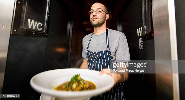 Chef Sam Strow carries one of two dishes an tripe stew with heirloom tomatoes and turnips toward the judges during a monthly chef competition Chefs...